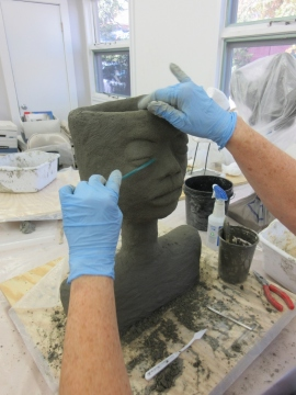 Student carving a face onto her sculpture in concrete